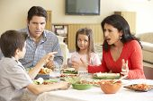 stock photo of hispanic  - Young Hispanic Family Enjoying Meal At Home - JPG