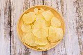 picture of potato chips  - Potato chips in wooden plate on white wooden table background - JPG
