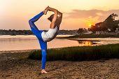foto of tantric  - Female Yoga Model Doing Dancer Pose Beach - JPG