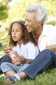 stock photo of grandmother  - African American Grandmother And Granddaughter Blowing Bubbles In Park - JPG