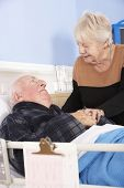 stock photo of visitation  - Senior woman visiting husband in hospital - JPG