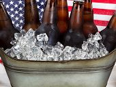 stock photo of tub  - Close up of cold beer and ice in steel tub with American flag in background - JPG