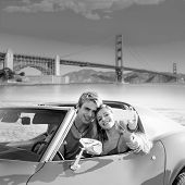 stock photo of golden gate bridge  - selfie of young teen couple at convertible car in San Francisco Golden Gate Bridge photo mount - JPG
