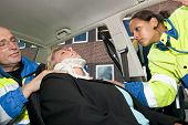 stock photo of neck brace  - Paramedics placing a neck brace on an injured woman inside her car after a car crash - JPG
