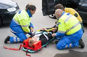 stock photo of stretcher  - Paramedics and a fireman strapping a wounded woman with a neck brace on a stretcher - JPG