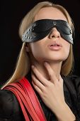 stock photo of sadist  - Portrait of young beautiful woman in studded blindfold - JPG