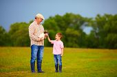 picture of grandpa  - grandson playing with dog puppy on grandpa - JPG