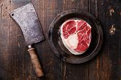 picture of veal  - Raw fresh cross cut veal shank for making Osso Buco and meat cleaver on dark wooden background - JPG