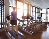 foto of treadmill  - Healthy man and woman running on a treadmill in a gym - JPG