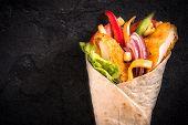 stock photo of sandwich wrap  - Popular chicken wrap sandwich on black background with blank space - JPG