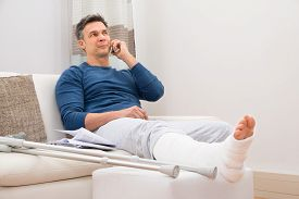 image of fracture  - Man With Fractured Leg Sitting On Sofa Talking On Cellphone - JPG