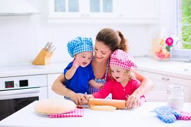 stock photo of little sister  - Kids and mother baking - JPG