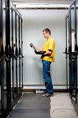 stock photo of console-mirror  - The engineer stand in datacenter near telecomunication equipment - JPG