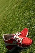 Red Running Shoes On A Sports Field