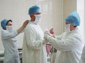 Nurses are covering surgeon on sterile dress