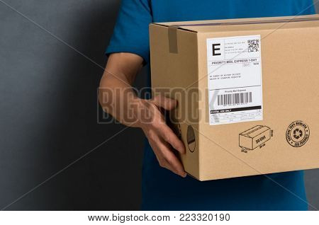 poster of Closeup hands of delivery man holding package to deliver. Courier hand holding brown box isolated on