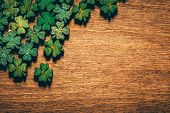 Green wooden four leaf shamrocks laying on a wooden board. St. Patricks day. Irish culture. poster