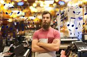 music, sale, people, musical instruments and entertainment concept - male assistant or customer with poster