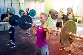 fitness, sport, training, exercising and lifestyle concept - group of people with barbells doing sho poster