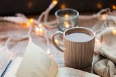 hygge and cozy home concept - book and cup of coffee or hot chocolate on table poster