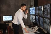Male security guard using radio transmitter in surveillance room poster