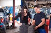 A mechanic showing the tread of a tire to a female customer