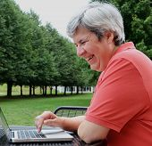 Middle-aged Woman Browsing On Laptop Outside