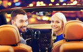 vehicle, luxury and people concept - happy couple driving in convertible car over night city lights  poster