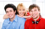 Three young students looking at camera and smiling