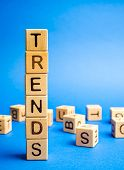 Wooden Blocks With The Word Trends. Popular And Relevant Topics. New Ideological Trends. Recent And  poster