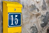 Yellow Postbox On Stone Wall. Mailbox With Number 15. poster