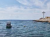 Rocky Coastline Of Saronic Gulf, Aegean Sea, Boat And Memorial Cross At Piraeus, Attika, Greece. poster