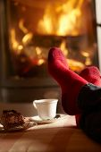 Close Up Of Mans Feet Relaxing By Cosy Log Fire With Tea And Cake