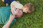Hug On Green Grass - Grandfather And Grandson. Happy Senior Man Grandfather With Cute Little Boy Gra poster