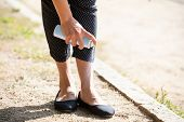 Low Section Of Woman Standing Outdoor Spraying Anti Insect Deet Spray On Her Foot poster