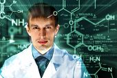 image of chemistry technician  - Young chemist in white uniform working in laboratory - JPG