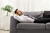 Businessman resting on gray sofa at home  poster