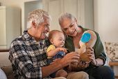 Toddler playing with old grandparents and teddy bear stuff toy. Cheerful grandfather and smiling gra poster