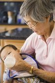 Asian grandmother feeding baby grandchild with bottle