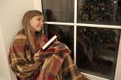 Cute Dreamer. Small Child Read Book On Christmas Eve. Small Reader Wrapped In Plaid Sit On Window Si poster