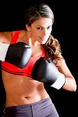 Female boxer wearing boxing gloves - isolated over a black background