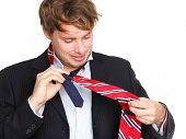 Necktie - man can not tie his tie. Young professional business man trying tying his tie getting read