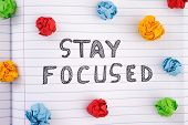 Stay Focused. Phrase Stay Focused On Notebook Sheet With Some Colorful Crumpled Paper Balls Around I poster