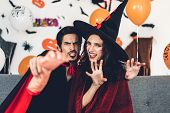 Couple Having Fun Wearing Dressed Carnival Halloween Costumes And Makeup Posing With Bats And Balloo poster