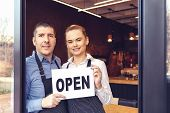 Two Cheerful Small Business Owners Smiling And Looking At Camera While Standing At Entrance Door - H poster