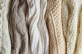Pile Of Knitted Sweaters Of Different Colors And Patterns Perfectly Stacked. poster