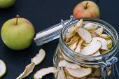 Homemade Organic Dried Apple Chips In Glass Bottle With Fresh Apple poster