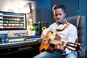 Contemporary young musician or guitarist in casualwear playing guitar while sitting in sound recordi poster