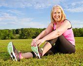 Mulher de meia-idade em seu 40s, estendendo-se para exercício ao ar livre