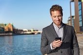 Business man texting on mobile phone using app for sms text message 5g technology. Young Caucasian b poster